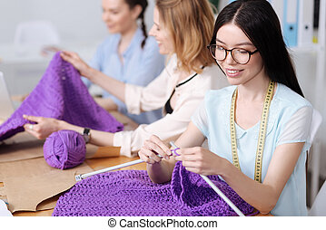 Three women knitting purple scarves - Handicraft time....