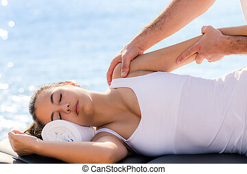 Woman having osteopathic shoulder treatment outdoors.