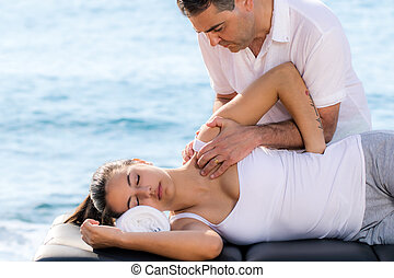 Male therapist doing shoulder treatment on woman outdoors.
