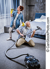 Couple with vacuum cleaner - Happy mature couple having fun...