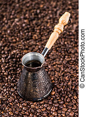 Elevated view of turkish coffee pot on coffee beans