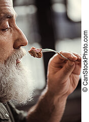 Man eating steak - Close-up profile portrait of bearded...