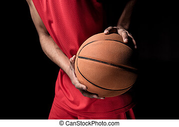 Close-up partial view of young sporty man holding basketball...
