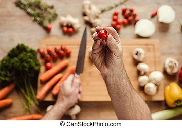 Man preparing vegan food - Partial top view of man holding...