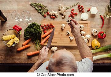 Man preparing vegan food - Overhead view of senior man at...