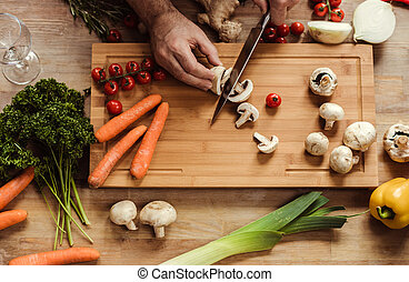 Man preparing vegan food - Partial top view of man chopping...