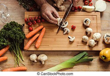 Man preparing vegan food - Partial top view of man chopping...