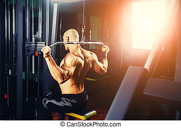 power athletic guy bodybuilder, execute exercise with gym...