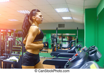 Young fitness woman doing cardio exercises at the gym...
