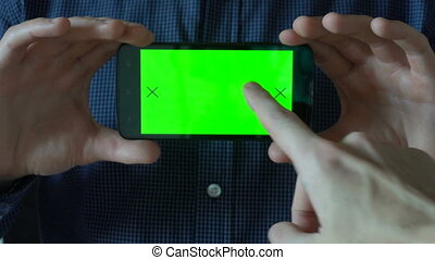 young man in shirt holding phone with green screen in front of him