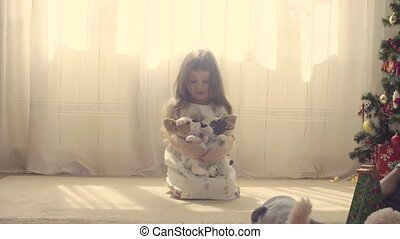 A girl sitting on the floor with two stuffed dogs