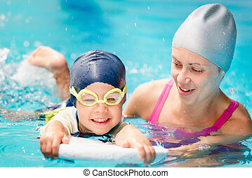 Little boy learning to swim with instructor's help