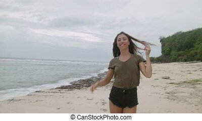 Happy tanned girl with long hair walking along the sandy...