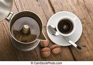 coffeepot and cup of coffee with chocolate cookies on wooden...