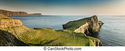 Neist point Lighthouse in light of setting sun. Landscape of...