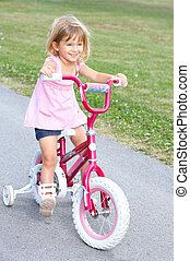 girl - smiling little girl cycling  in the park