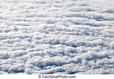 Flying high above white clouds.