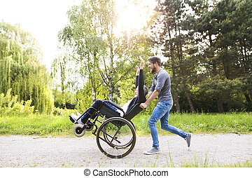 Hipster son running with disabled father in wheelchair at park.