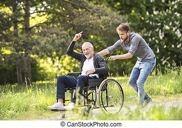 Hipster son walking with disabled father in wheelchair at park.