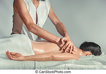 Massage oil therapy. A young professional male masseur makes...