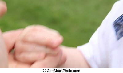 parent hand holds his baby hand - Newborn baby boy holds his...