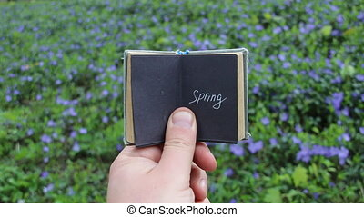 Spring concept, book with text and spring field with blue...