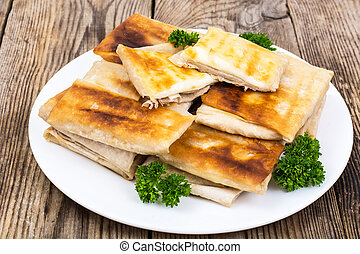 White plate  with envelopes of thin Armenian bread lavash fried with crispy crust. Filling of cheese and greens for hot breakfast