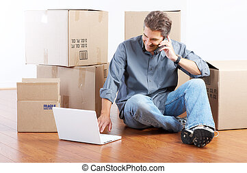 Moving - Handsome man with boxes in the new apartment after...