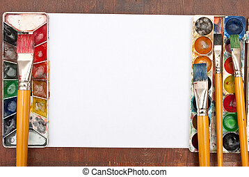 Watercolor paints set with brushes and paper sheet
