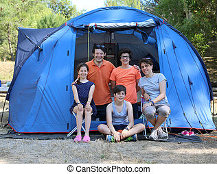 Happy family with three smiling children and tent in summer camping