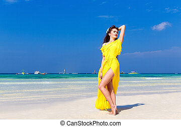 Beautiful brunette woman in a yellow dress on the tropical sea coast in sunny day. Summer vacation concept.