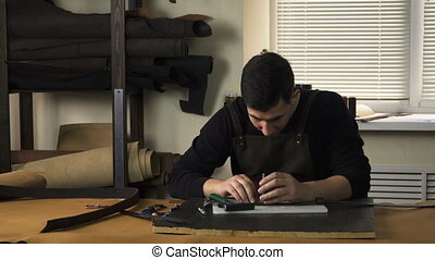 Craftsman working with a piece of leather on the table....