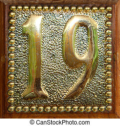 Nineteen - Brass and wood plaque with the number nineteen...