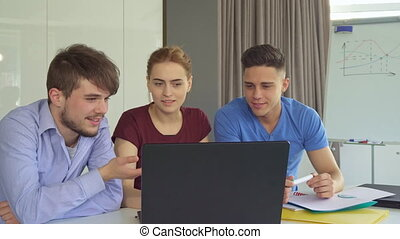 Young people discuss something on laptop at the office