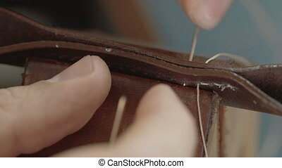 Stitching leather manually. - Closeup view of man's hand...