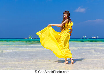 Beautiful brunette woman in yellow dress with her back to the viewer on the tropical coast of the sea in a Sunny day. Summer vacation concept.