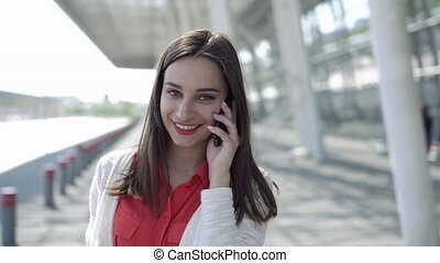 Woman in red shirt talks on the phone walking