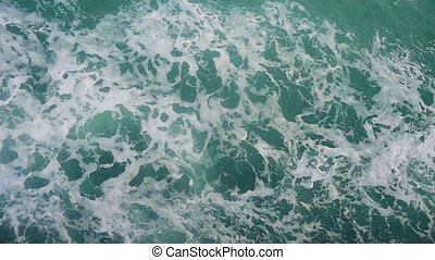 Powerful waves pulled out from fast moving boat, a huge stream of deep blue water with white foam rising up in slow motion