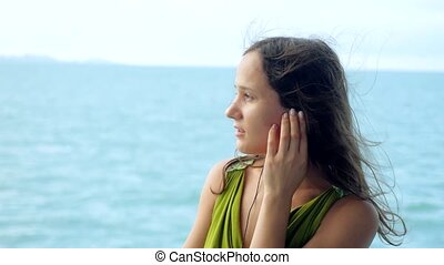 Beautiful dreamy young woman listening to music on...