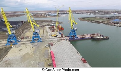Aerial port crane bridge and bulk carrier. Close up view Cargo freight ship and cargo container working with crane at port area,Logistic Import Export at night. Port cargo crane over sky