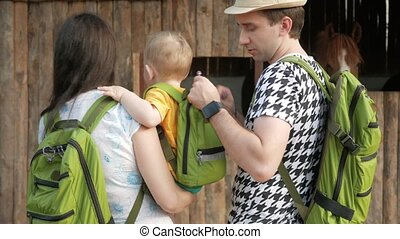 Young parents with a baby are looking at a stall with horses. All are wearing green backpacks.