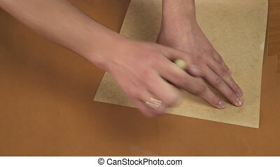 Man's hands transferring template to leather. Making a...