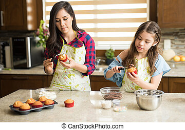 Mom and daughter decorating cupcakes