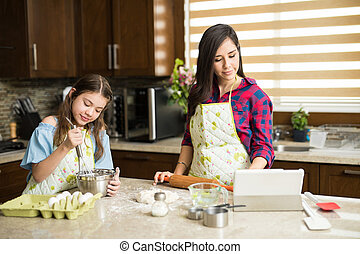 Mom and daughter following recipe