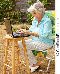 Working In The Garden - A senior woman using a laptop...