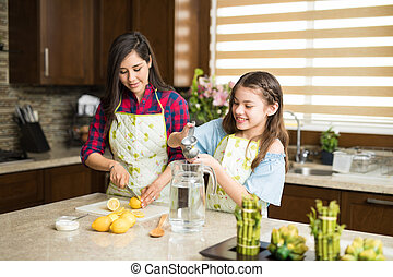 Mom and daughter squeezing lemons