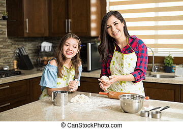 Mom and daughter having fun in the kitchen - Pretty Hispanic...