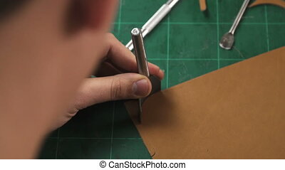 craftsman's hands working with a piece of leather - Closeup...