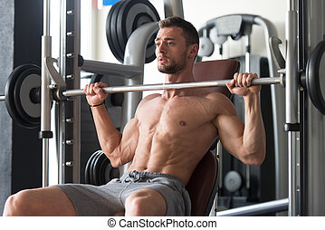 Shouder Exercises With Barbell - Muscular Man Doing Heavy...