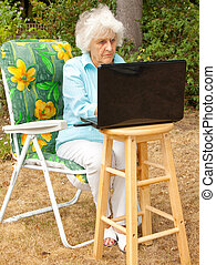 Outdoor Internet Connection - An elderly woman using a...